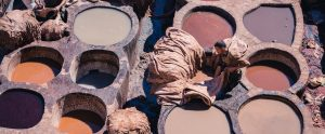 outdoor leather tanning vats with dye and a person standing on top